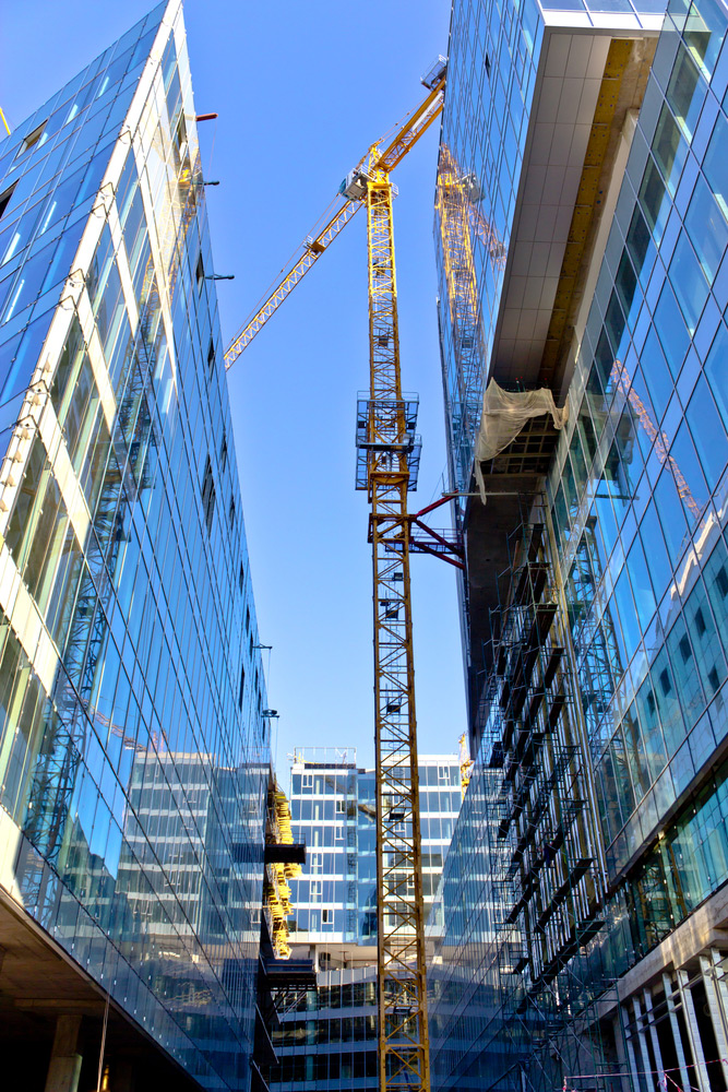 Tall buildings under constructions with tall cranes and scaffolding