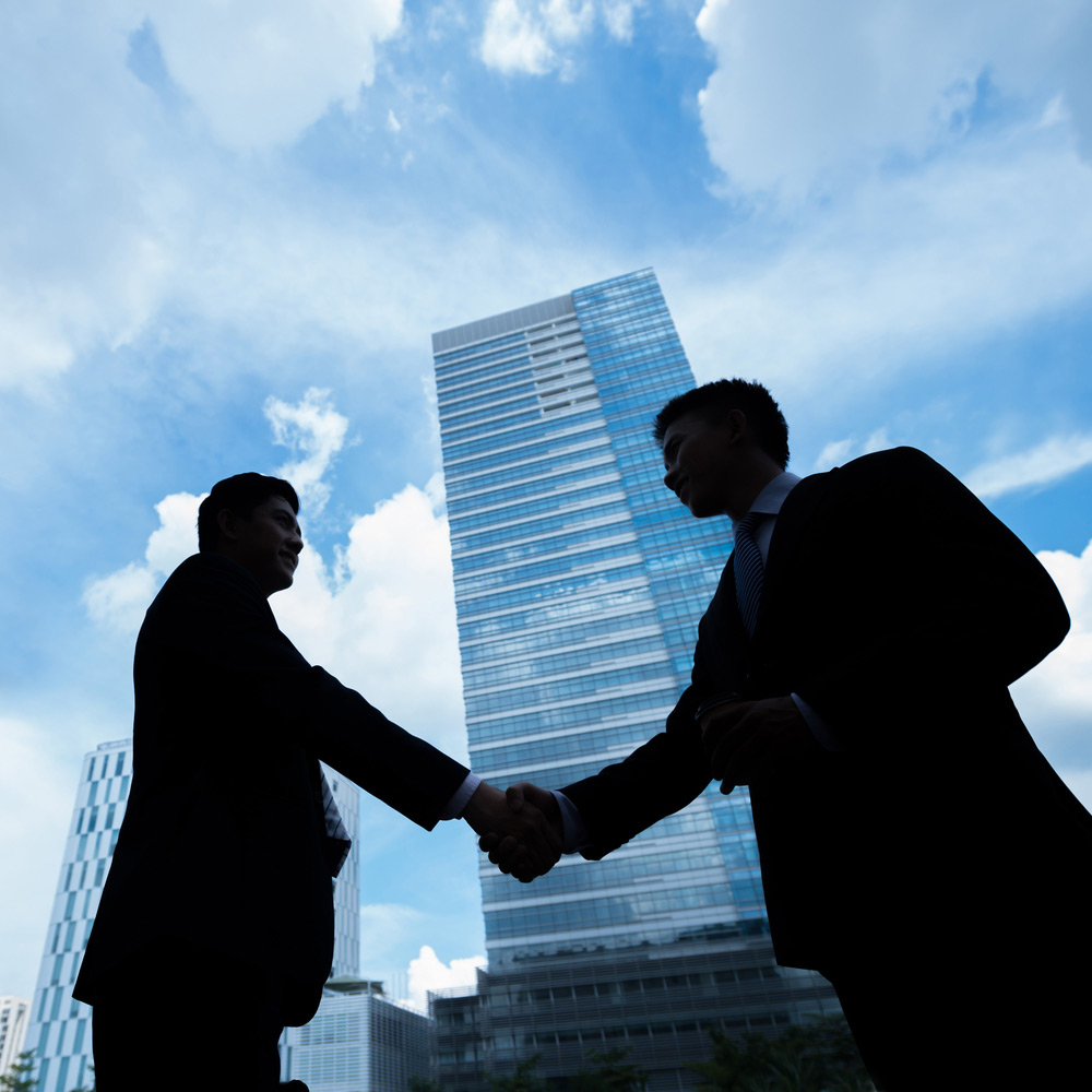 Two Business People Shaking Hands in front of tall building