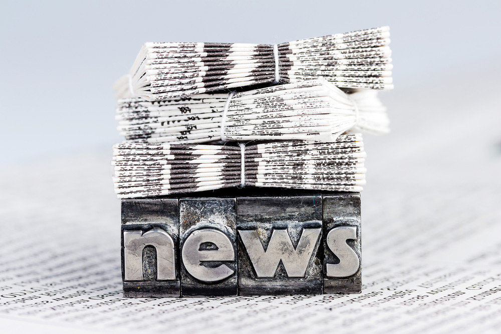 stock photo of newspaper stacks laying on top of a block with the words news